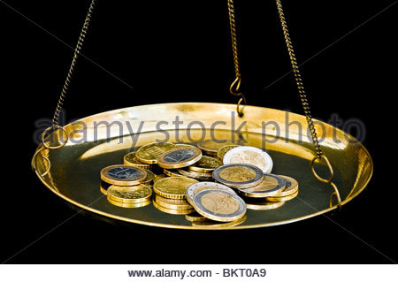 Euro coins on brass weighing scales - Stock Photo