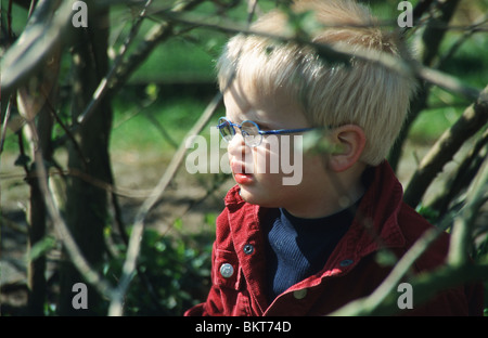 Shortsighted boy playing in park outside - Stock Photo