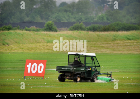 A golf ball collector on the rainswept driving range at the Celtic Manor Wales Open 2008 - Stock Photo