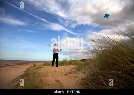 business man flying kite on beach - Stock Photo