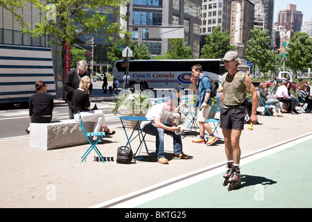 man roller blading passes outdoor public seating area on Broadway at Columbus Circle on a beautiful spring day in - Stock Photo