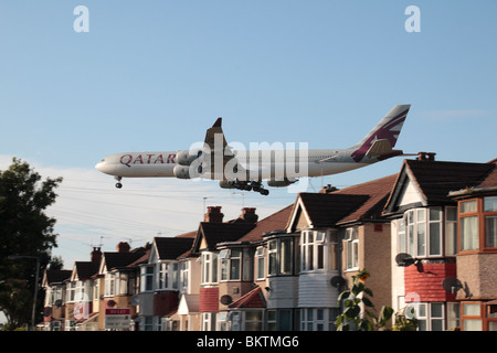 A Qatar Airbus A340-642 landing at Heathrow Airport, London, UK. View from Myrtle Avenue, Hounslow. (A7-AGC) - Stock Photo