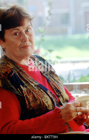 Old age woman serious look at camera drinking coffee and seated in front of window - Stock Photo