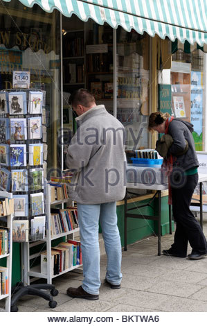 Shoppers browsing outside a bookshop in South Street, Dorchester, Dorset, England - Stock Photo