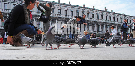 Tourists and pigeons in St Mark's Square, Venice, Italy - Stock Photo