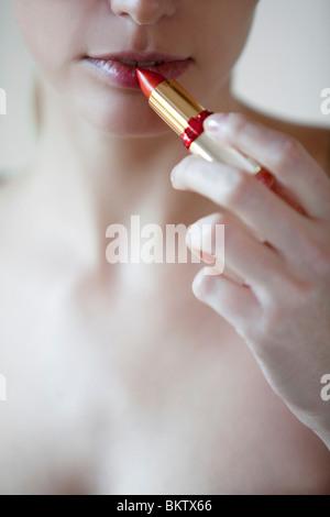 woman puts on lipstick - Stock Photo