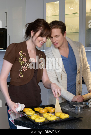 Man and woman baking lucia bun - Stock Photo