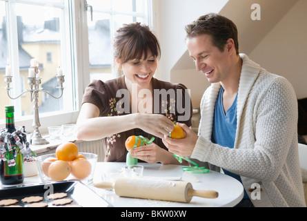 Woman and man decorating orange - Stock Photo