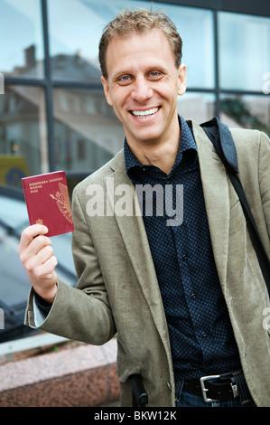 Man holding passport - Stock Photo