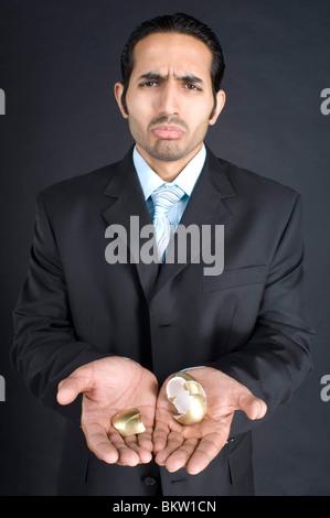 Businessman holding broken golden egg in cupped hands - Stock Photo