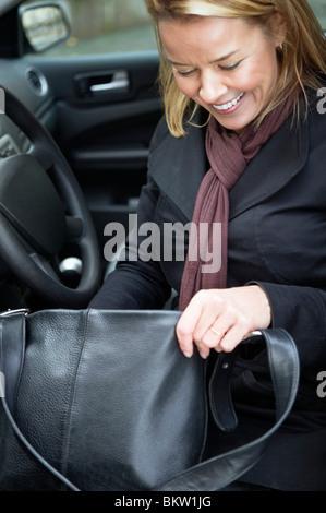 Woman with handbag in car - Stock Photo
