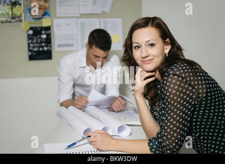 Portrait of woman at office, man reading in background - Stock Photo