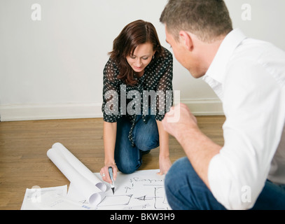 Two colleagues looking at blueprints on floor - Stock Photo