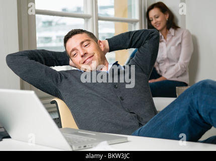 Man with hands behind head - Stock Photo