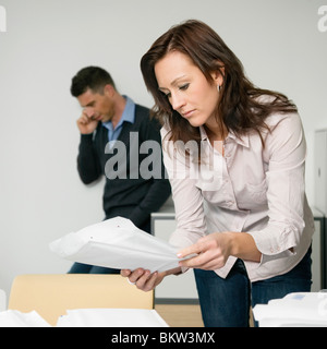Businesswoman holding documents, coworker standing in behind - Stock Photo