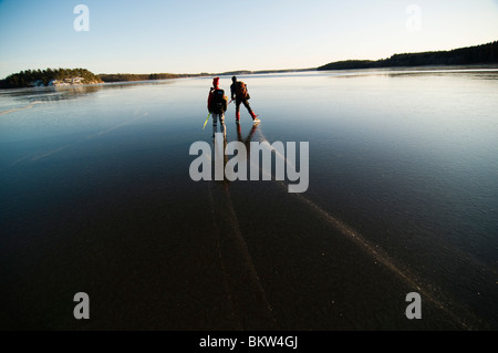 Two people skating on frozen lake - Stock Photo