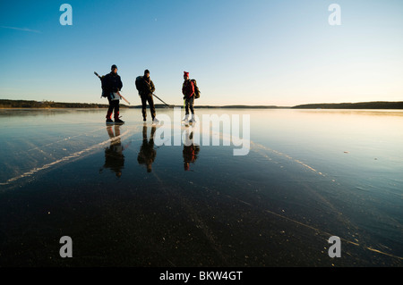 Three long-distance skaters standing on ice - Stock Photo