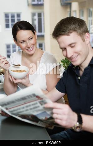 Couple reading newspaper - Stock Photo