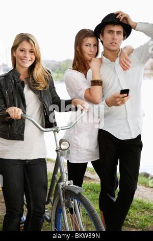 Three friends and a bike - Stock Photo