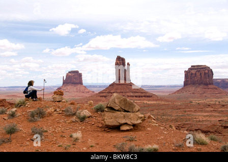 Hiker in foreground with the buttes and mesas of the Navajo Tribal Park in background Monument Valley Utah USA Kim - Stock Photo