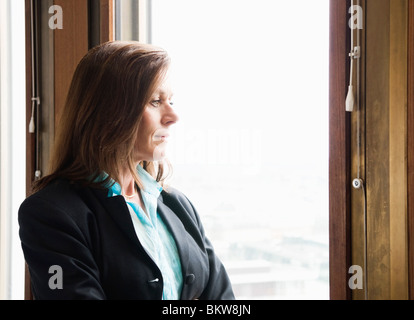 Businesswoman looking out through the window - Stock Photo