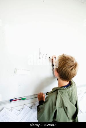 Short boy writing on whiteboard - Stock Photo