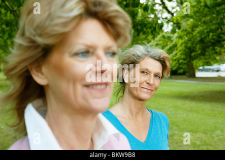 Two women standing in the park - Stock Photo