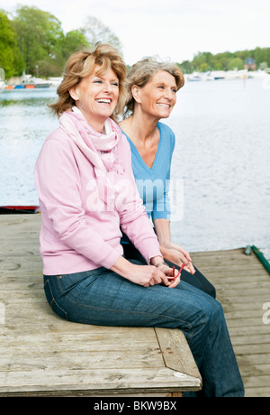 Two female friends sitting on a pier - Stock Photo