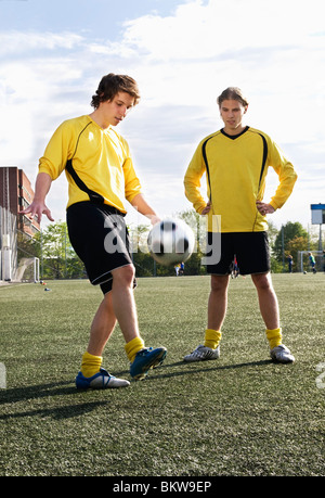 Two friends playing soccer - Stock Photo