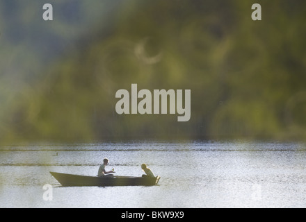 Two people in a small boat - Stock Photo