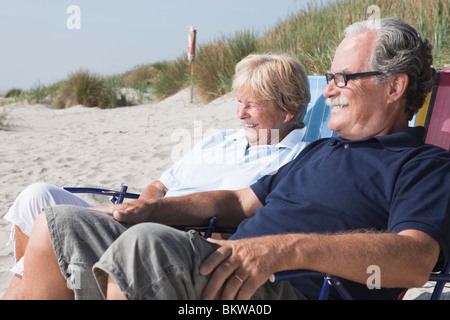 Two people sitting on the beach - Stock Photo