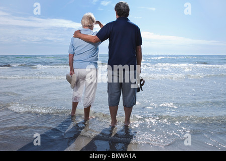 Couple looking out towards the water - Stock Photo