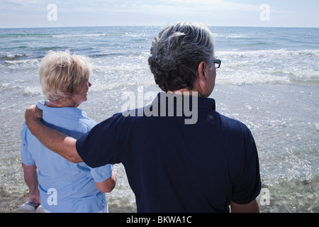Man and woman looking out over water - Stock Photo