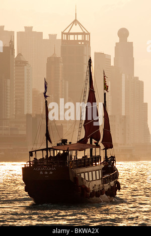 A traditional Chinese junk sailing in Hong Kong Harbour - Stock Photo