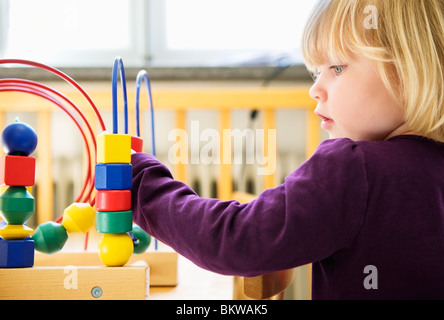 Little girl playing at daycare center - Stock Photo