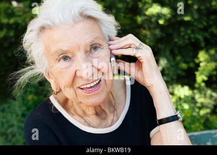 Elderly woman talking in phone - Stock Photo