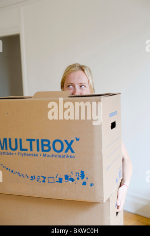 Woman standing behind moving boxes - Stock Photo