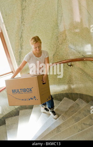 Woman carrying movingbox upstairs - Stock Photo