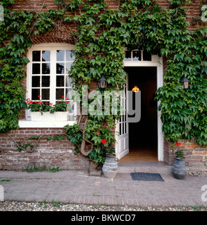 Lush green ivy vines around a window & door of an 1825 farmhouse and grist mill, Sept-Meules, near Eu, Normandy - Stock Photo