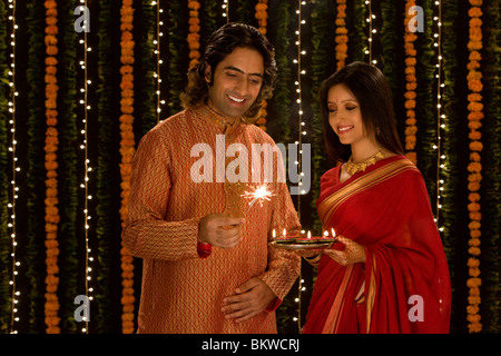 Indian man holding a small fire work and woman with a plate of candles - Stock Photo