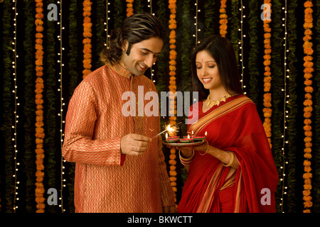 Indian man lighting a small fire work and woman with a plate of candles - Stock Photo