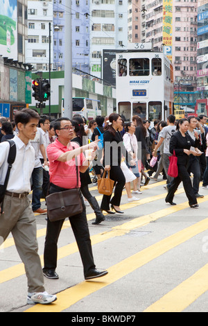 People crossing the road in front of trams in Hong Kong - Stock Photo