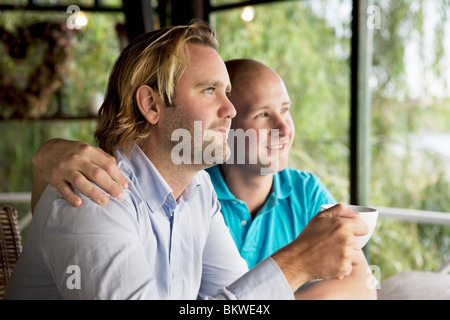 Two men looking out the window - Stock Photo