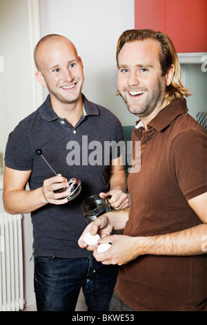 Two men standing in the kitchen - Stock Photo