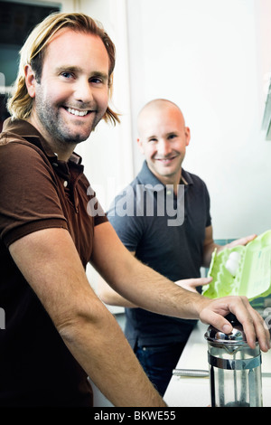 Two men fixing in the kitchen - Stock Photo