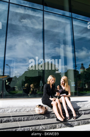 Two businesswomen sitting in stone stair making plans - Stock Photo