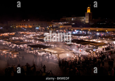 Charcoal smoke rising over the food stalls of Place Djemaa el Fna at night with people eating in the Medina quarter - Stock Photo