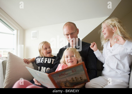 Father reading for three daughters - Stock Photo