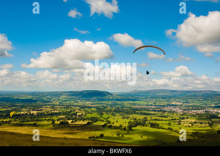 Paraglider above the Ribble Valley, Lancashire, England, seen from the launching site on Pendle Hill - Stock Photo