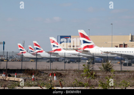A line of British Airways planes parked close to the southern perimeter waste ground of Heathrow Airport. Apr 2010 - Stock Photo